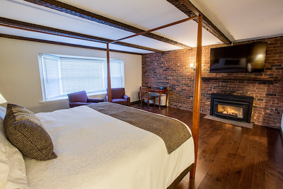 A fireplace king room with a canopy bed and wood flooring