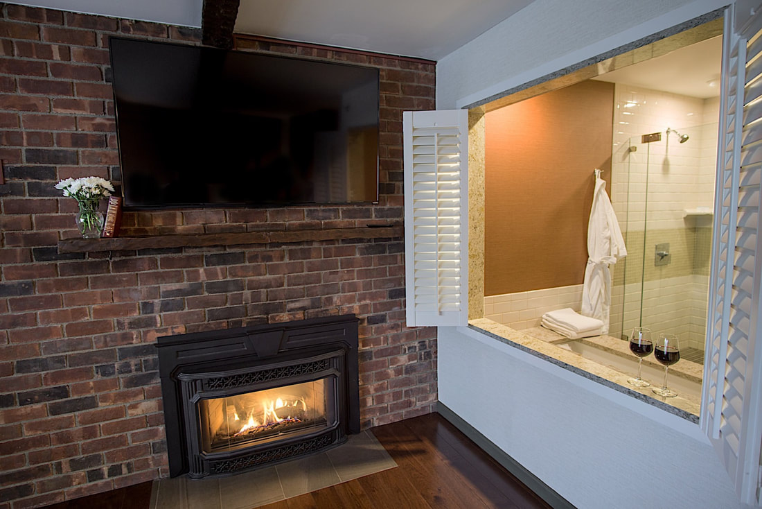 A spacious suite with a fireplace, large tv and a huge bathroom