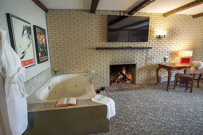 A jacuzzi suite with a jacuzzi tub, fireplace, and a large TV