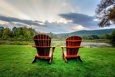 Adirondack chairs on a patch of green grass facing the mountains